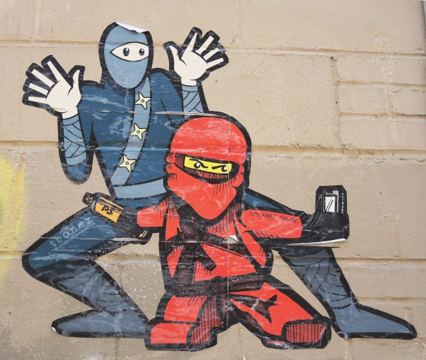 urban ninja squadron man with planet_selfie character in red with red helmet, pasteup on a wall