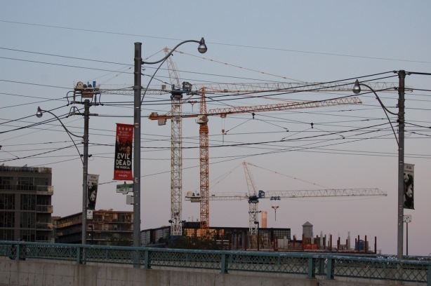 evening light, cityscape with many construction cranes, light poles and utility poles and wires, evening,