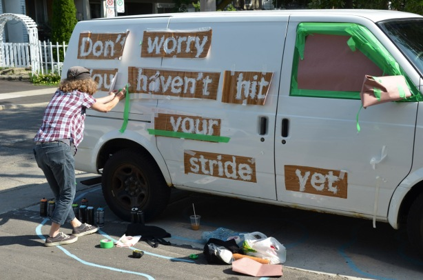 a woman is taping stencils onto the side of van. The stencils are of words, Don't worry you haven't hit your stride yet
