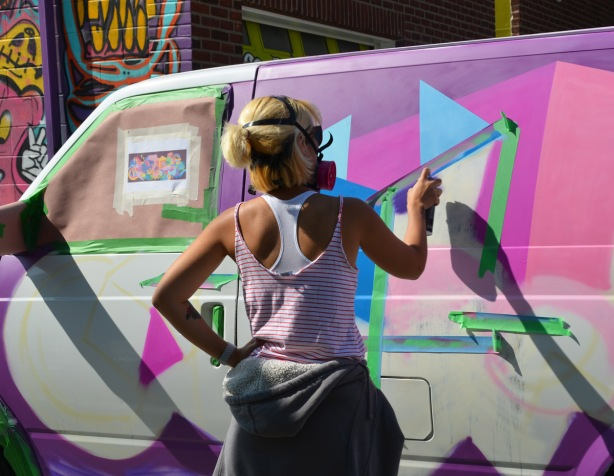 a woman spray paints on the side of a van that is being covered with street art, masking tape to keep the spray paint in straight lines.