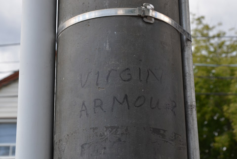 black sharpie words on a concrete utility pole, says Virgin Armour