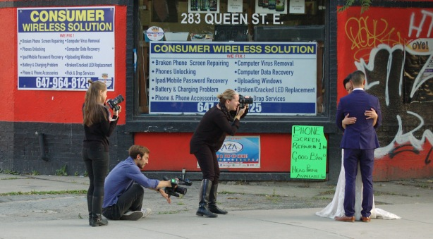 a bride and groom embrace while three photographers take their picture. on a sidewalk of a city street