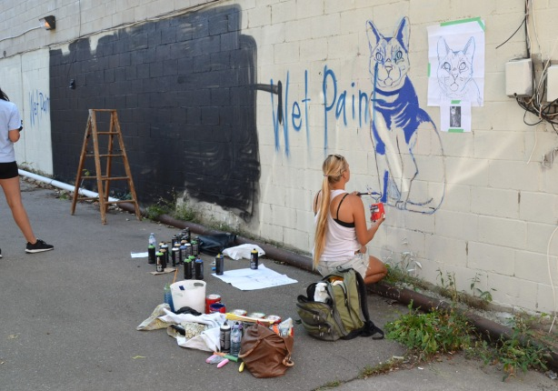 a woman is crouching beside a wall where she is painting a picture of a blue cat, on the wall beside her is a large black section that has just been painted in preparation for another mural