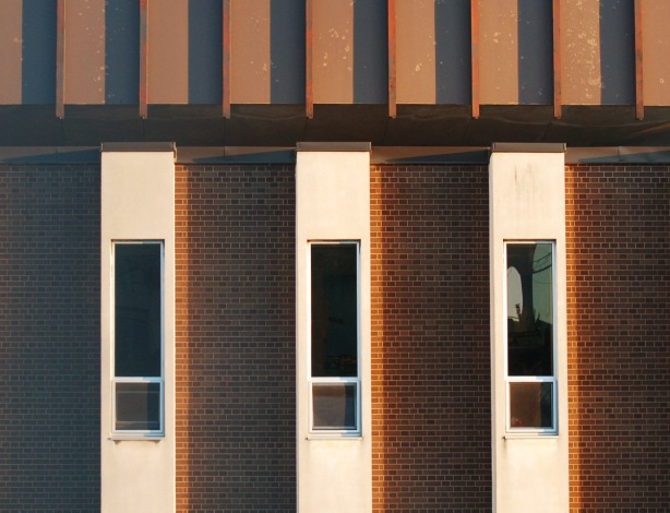 part of a wall, vertical stripes of brick sections and white sections, narrow windows in the white sections, 3 windows in total