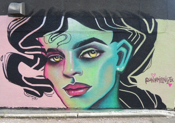 street art mural of a woman's face in greens and blues on one side, moving to pink on the other, lots of black hair. red lips, yellow eyes