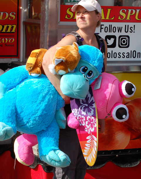 a woman carrying two stuffies and a skateboard, one is a large blue dinosaur and the other is a large pink creature