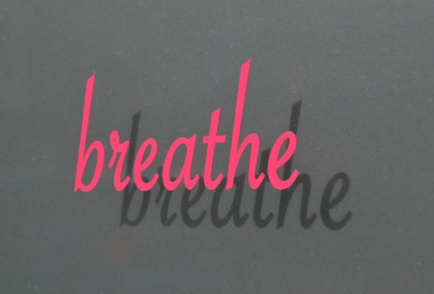 the word breathe is painted in pink on a window, the sun makes a shadow of the wod on a blind behind the window.