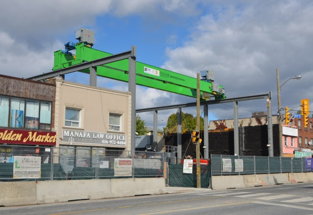 a large horizontal crane stretches over a vacant lot where a subway station is being built