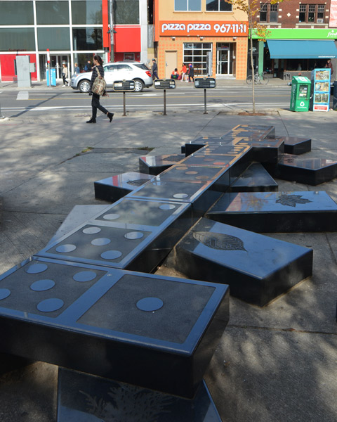 sculpture of very large black dominoes on sidewalk, street and shops in the background, including a Pizza Pizza restaurant