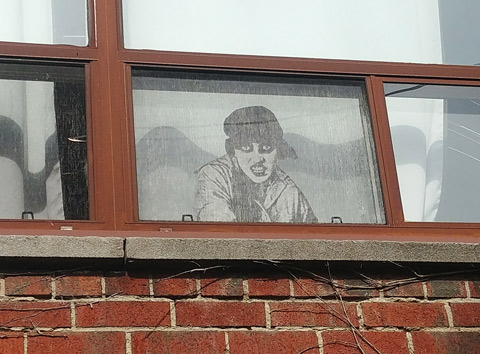 black and white realistic drawing of a sneering woman with a hat on looking out of a window on the second storey of a brick building.