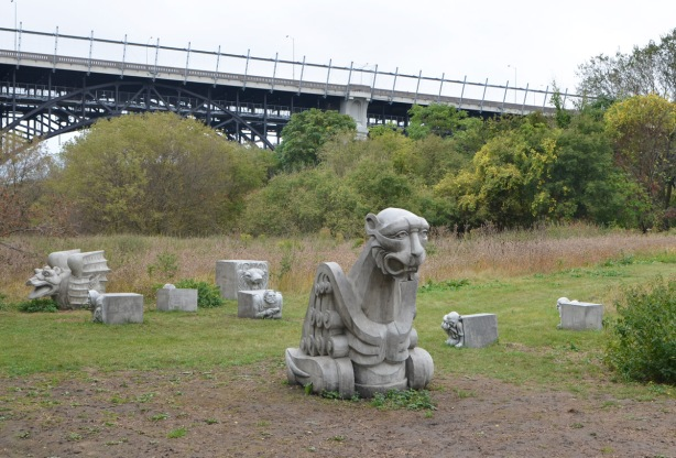 a few concrete gargoyles scattered on the ground by the Lower Don Trail, part of Duane Linklater's art installation.