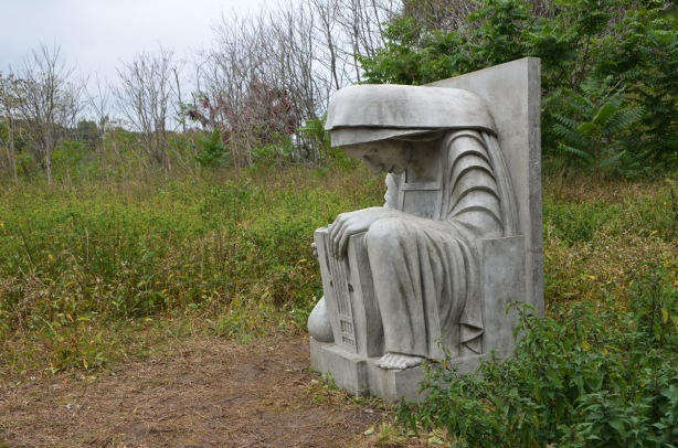 cast concrete sculpture of a seated woman with her head bent forward