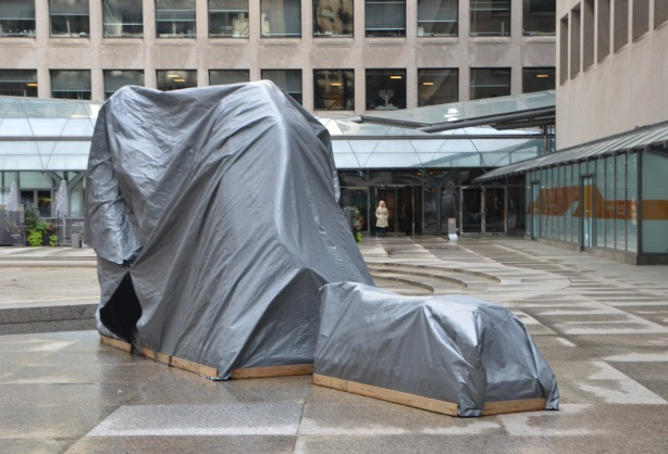 a sculpture in a public square is covered by grey plastic