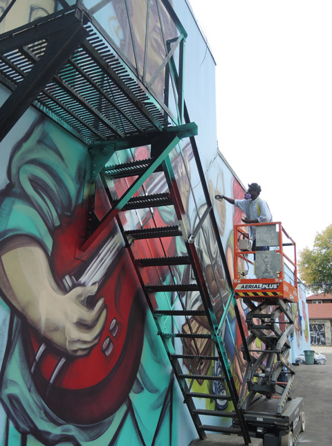 elicser works on painting a mural, in the foreground is a large painted guitar player with a red uitar, painted behind a metal fire escape staircase