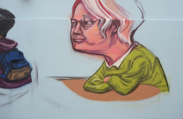 partially finished man with green sweater, grey hair, elbows on table