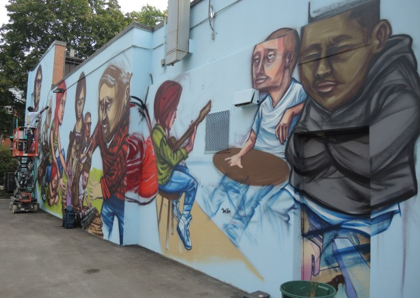 view of most of a long horizontal mural on the side of a building in an alley, by elicser, who is in the picture, painting, mural is of people doing various things.