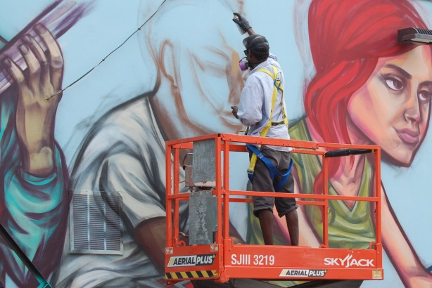 street artist, elicser elliott, up on a lift as he spray paints the outlines of a man's head as part of large mural that he is working on.