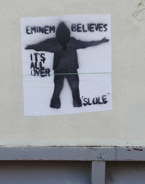 stencil, black on white, pasteup, black man in silhouette with his arms out, with words that say Enimem believes it's all over, slole