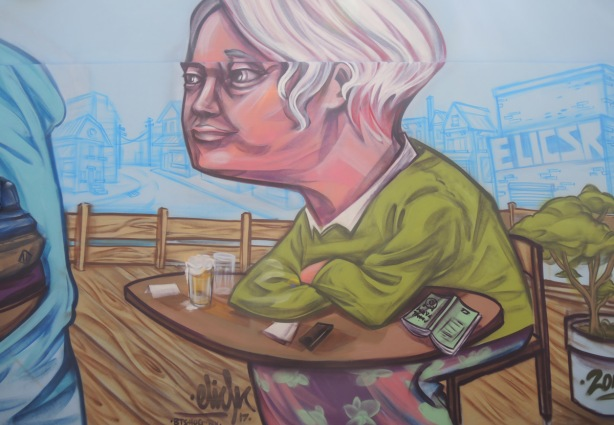 finished section of a mural, with man with grey hair sitting with elbows on a table,