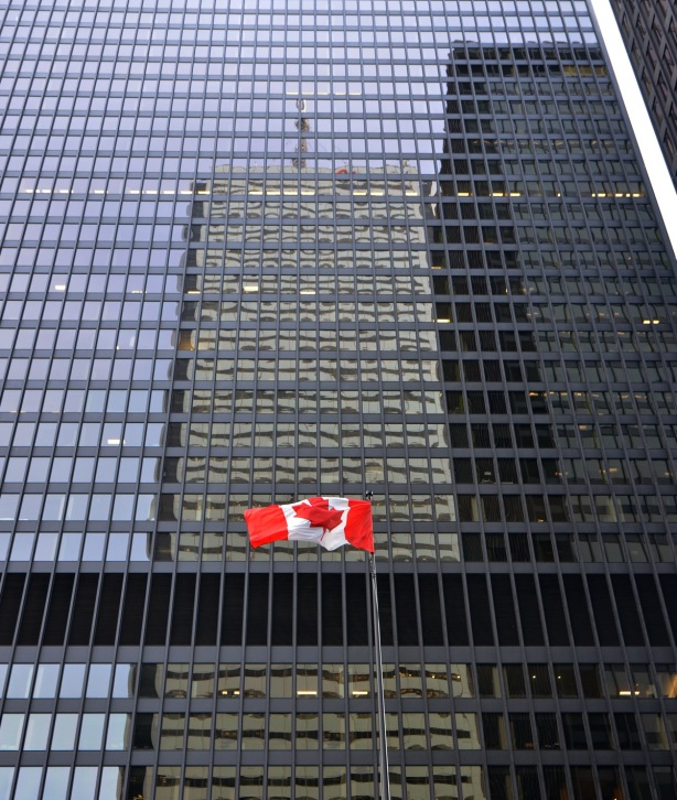 reflections in the black Commerce Court buildings, with a Canadian flag flying in front of the building.