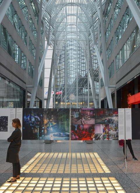glass ceiling of the Alan Lambert Galleria in Brookfield place with the world press photo exhibit underway, people looking at the posters