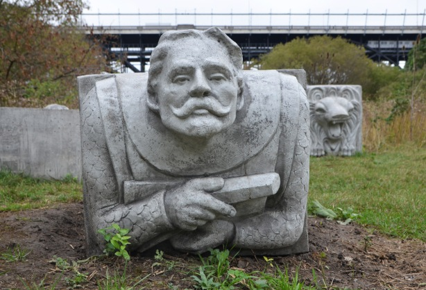 a concrete block and man's head gargoyle, with moustache, folded arms holding a scroll or similar), about 2 feet square, Bloor Viaduct in the background