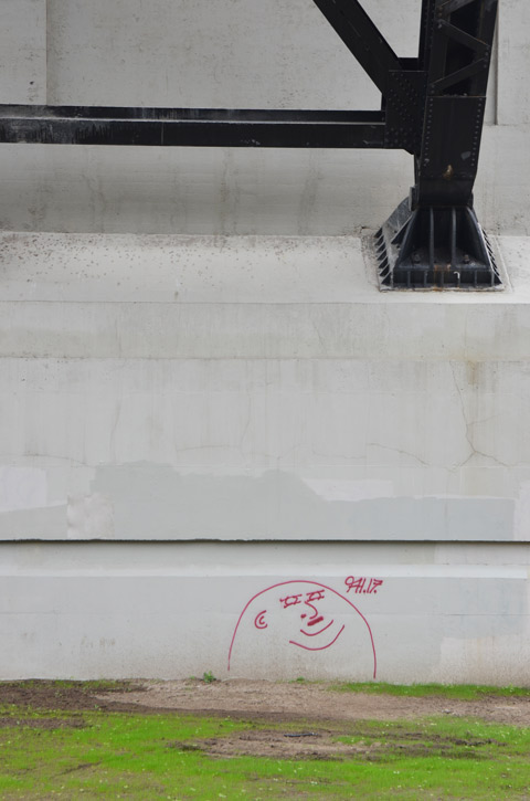 grey concrete bridge with black metal supports, part of the structure, with one graffiti face drawn in red