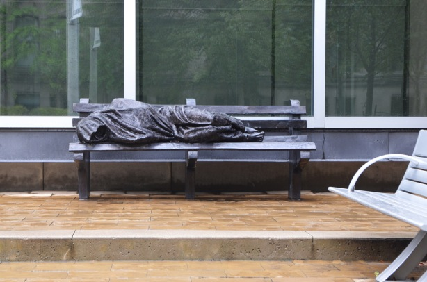 a sculpture of a cloth covered person sleeping on a bench, in front of a large window, with a white bench nearby