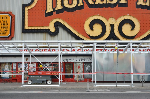 the start of grey hoardings going up around the old Honest Eds store on Bloor Street as preparations are made to demolish it