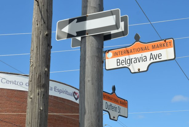 street sins on a pole, a one way sign, plus two signs with street names, Belgravia Ave and Dufferin Street, both with orange tops that have the words International Market