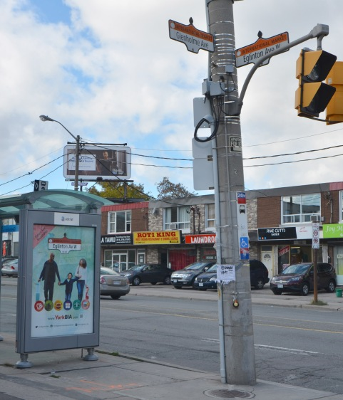 street scene on Eglinton Ave with bus shelter, utility pole, street signs, stores, and billboard