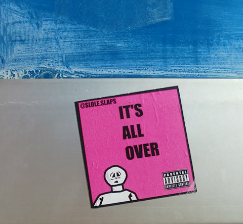 a small pink square sticker with a stick drawing of a man's head and shoulders, with words that say It's all over