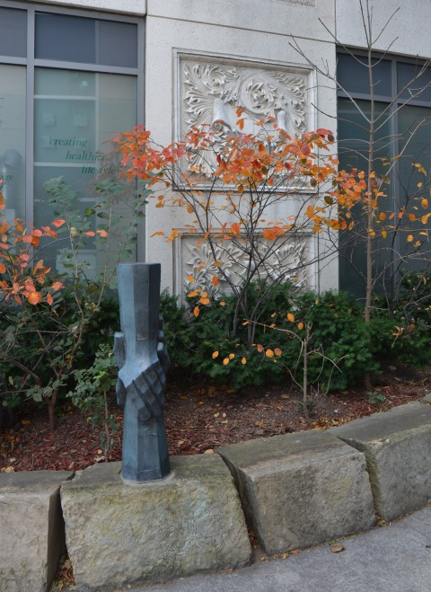 a small sculpture of two hands holding, vertical, one hand from above and the other from below, in a small garden with some shrubs with autumn foilage, orange colours