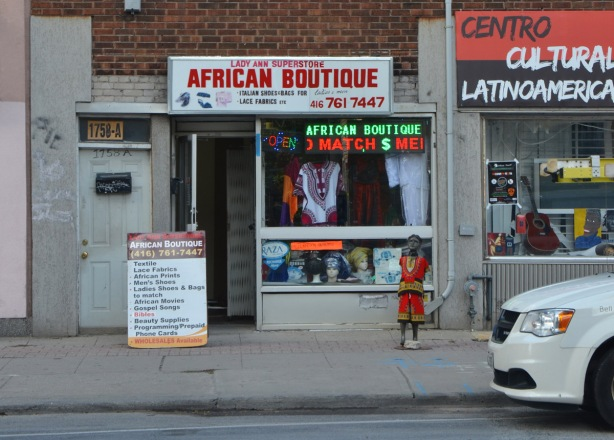 storefront, Lady Ann Superstore African Boutique with a mannequin, child size, on the sidewalk outside dressed in red African style clothes.