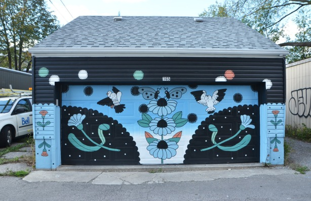mural on an alley garage, black and blue predominant colours, some flowers, and birds