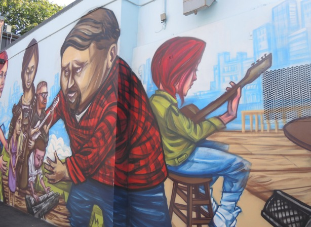 part of a mural by elicser of people - a woman is sitting on a stool and playing a guitar, a man in a red and black checked shirt