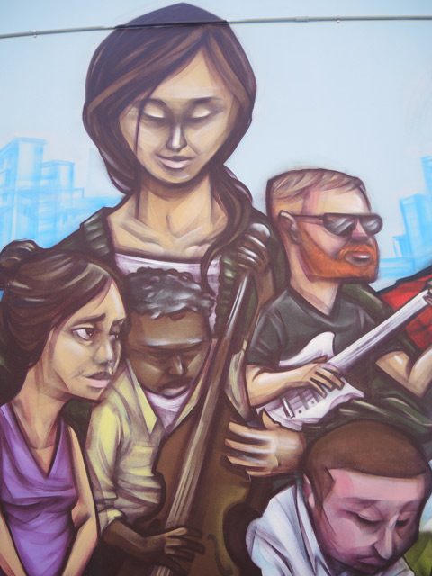 part of a mural by elicser of people - 4 people, a woman overlooks them, a small black man on a cello and a man with beard and glasses on a white guitar.