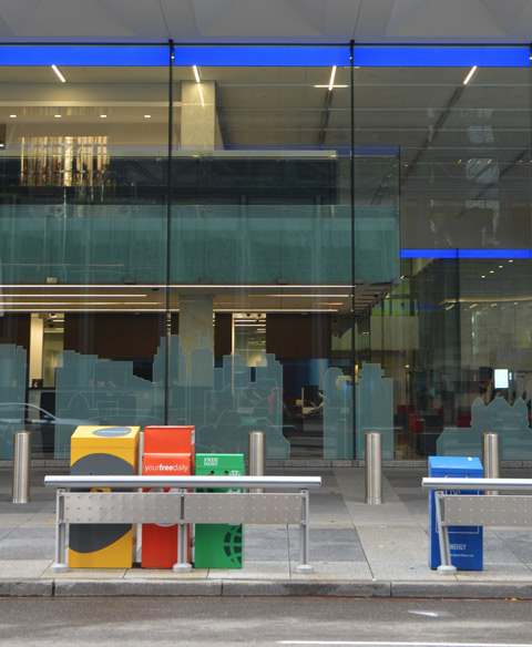 newspaper boxes in different colours in front of a large window of the BMO building, a city scape is etched into the window. Some reflections in the window too