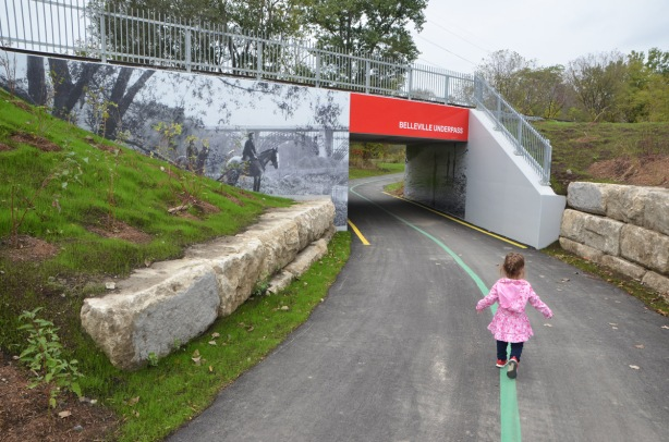 little girl in a pink jacket is wlking down a green line that is painted in the middle of a path, approaching an underpass under the railway tracks.