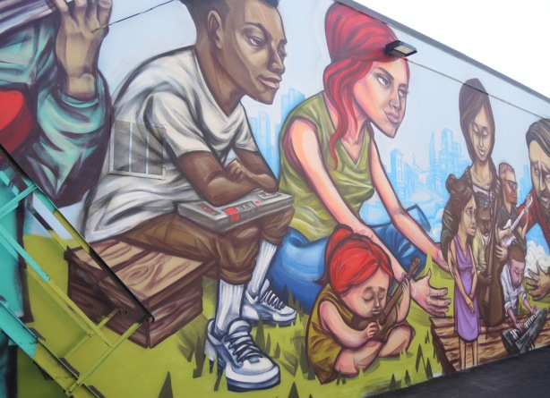 mural, part of, by elicser, people sitting outside, a young child with red hair sits on the grass, her mother behind her. A black man sits on a wooden seat, a cassette player on his lap