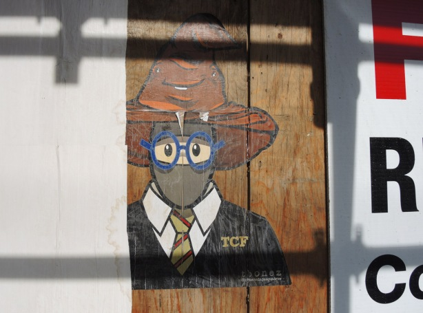 a large tbonez pasteup of an urban ninja squadron character, head and shoulders, but wearing a shirt and tie and blue rimmed glasses, also a brown pooh hat on his head.
