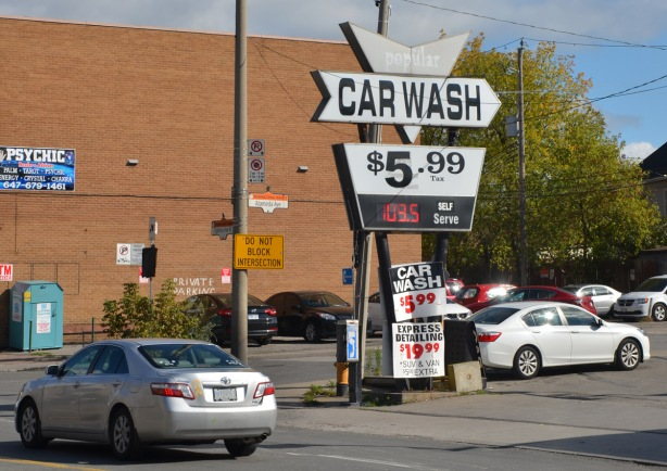 an old sign for popular car wah, $5.99 in front of a gas station