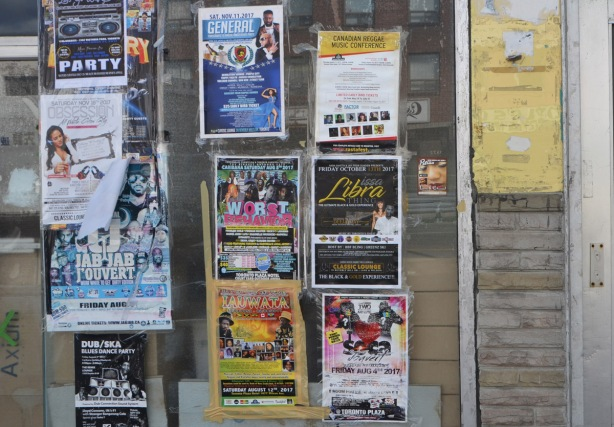 a window of an empty store that is covered with posters