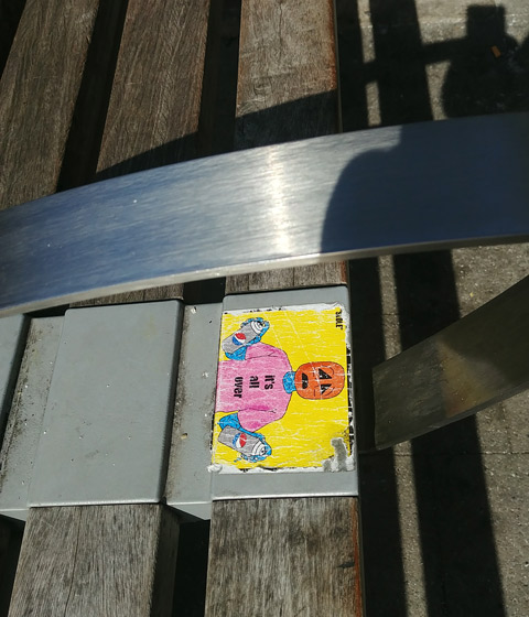 sticker on a bench, it's all over, with pumpkin head