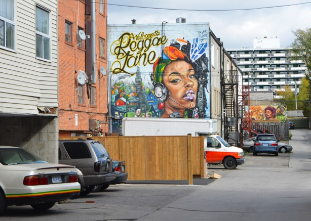 view looking down an alley, cars parked behind buildings, two murals, Welcome to Reggae Lane,