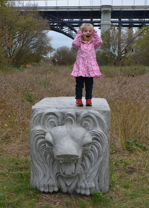 a young girl stands on top of a conrete block with the face of lion, she has her hands beside her mouth as she too roars like a lion