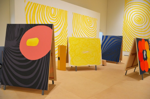 artwork by sandra Meigs at the Art Gallery of Ontario, paintings back to back, standing on the floor, bright colours, banners hanging on the walls of concentric yellow circles on white