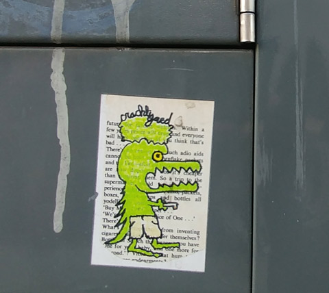 a sticker on the side of a grey metal box, a green alligator like character, walking on two legs, with a green head on top (two heads), drawn on white background that had words printed on it.