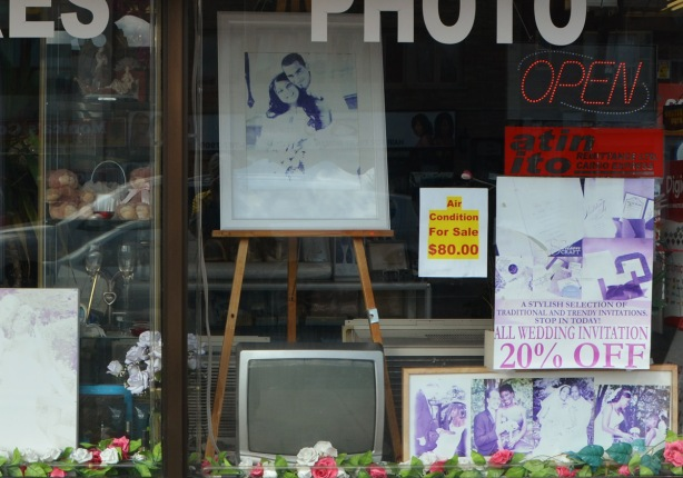 looking in the window of a store that sells photo frames and such, an old TV sits in the window too. The pictures are all faded to shades of blue and purple