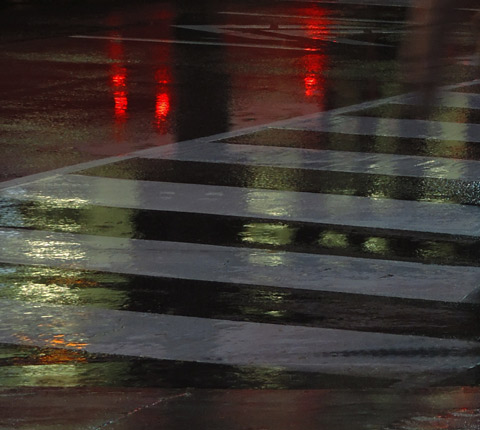 lights reflecting on a wet street, crosswalk